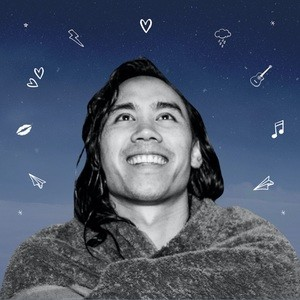 Promo image for 500 Nights Of Winter. Gene Phoa is pictured in medium close up smilinmg and gazing upwards against the background of a twilight sky. Icons arch around his head denoting ideas of music and love amongst other things.