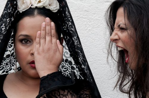 A Flamenco dancer dressed in black, medium close-up and facing camera covers her left eye as another dancer appears to be yelling into her left ear.