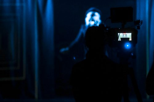 A darkened stage where a cabaret performer is about to hit the stage. Behind her is the screen of a digital camera, recording her every move.